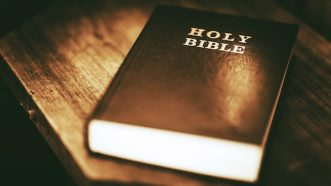 Holy Bible Closeup. Holy Bible on the Small Aged Wooden Table.